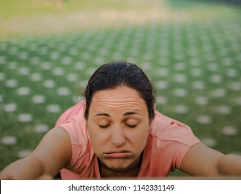 unmotivated sporty woman after fitness workout in the park outdoor making  grimace