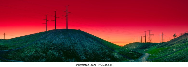 Unnatural Saturated Landscape with Electricity Pylons on the Hills. Red Moody Sunset in Silhouettes with Electric Poles and Cables. Strong Contrasting Backdrop Image with Space for Text or Design