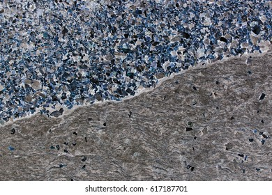 Unnaturally colored seaside pebbles and rock with sea shell