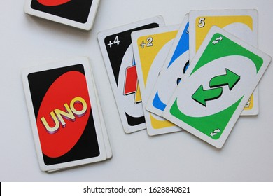 Uno cards during board game play in Moscow on January 2020. Uno game process with colorful printed deck isolated on white table background