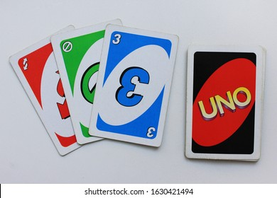 Uno playing cards in Moscow on January 2020. Uno board game process with colorful card deck isolated on empty white table background