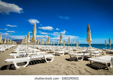 Unoccupied beach chairs in the sand on a sunny day in southern Italy.