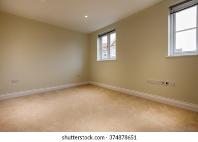 Unoccupied bedroom within brand new home with twin windows and carpet