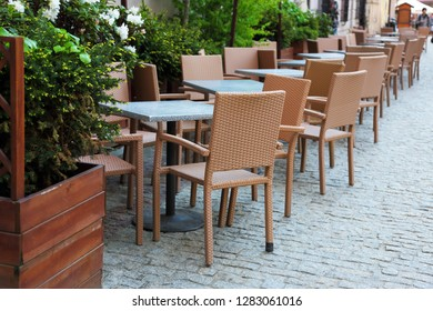 unoccupied restaurant tables on the street