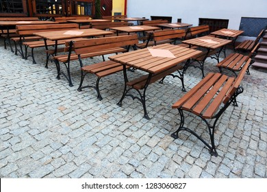 unoccupied tables with benches in the restaurant on the street