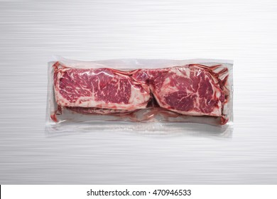 Unopened pack of 2 raw beef steaks on a polished aluminum kitchen table, without label