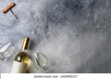 Unopened vintage bottle of white wine with blank label, empty wineglass & bunches of different grapes on wooden table background. Expensive bottle of chardonnay concept. Copy space, top view, flat lay