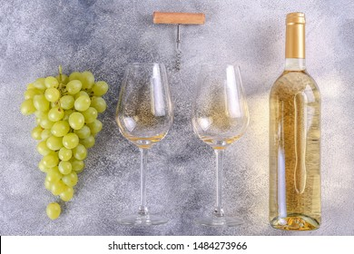 Unopened vintage bottle of white wine without label and bunches of ripe organic grapes on grunged stone table background. Expensive bottle of chardonnay concept. Copy space, top view, flat lay.