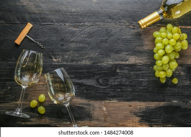 Unopened vintage bottle of white wine without label and bunches of ripe organic grapes on grunged wood table background. Expensive bottle of chardonnay concept. Copy space, top view, flat lay.