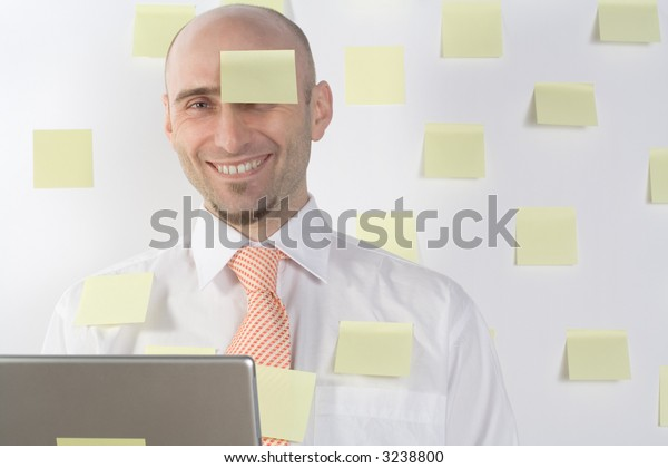 Unorganized businessman uses post-it notes to keep from forgetting important details and appointments.