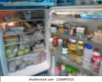 Unorganized fridge/refrigerator full with fresh foods, bottles and containers