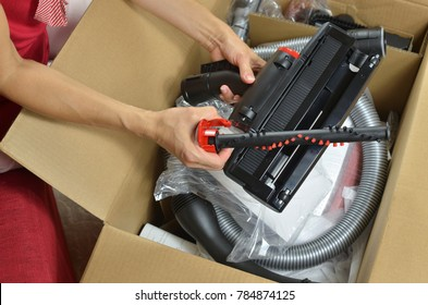 Unpacking a new red vacuum cleaner and its pro animal brush