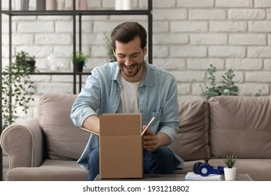 Unpacking parcel. Happy young man postal delivery service client sit on couch at living room open small carton box enjoy goods received. Curious guy online shopper get new order from web store by mail