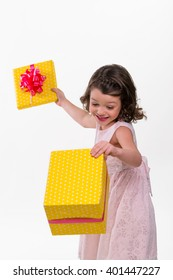 Unpacking the present box with a little gorgeous princess in pastel pink dress and nice hairstyle. White background in a studio. Bright moment of life.