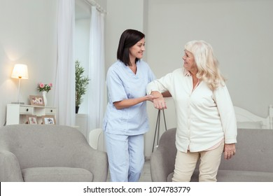 Unpaid work. Cheerful caregiver helping senior woman who smiling