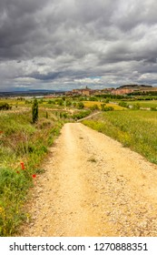 Unpaved country road on the Way of St. James, Camino de Santiago leading to the town of Viana in Navarre, Spain, a pilgrim in the distance