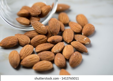 Unpeeled brown almond nuts in glass bowl on marble background