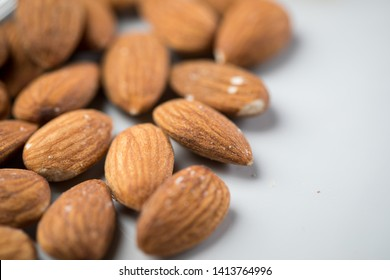 Unpeeled brown almond nuts on marble background