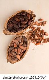 Kakaobohnen ohne Schale und frisch geröstet auf beigem Hintergrund. Superfood.