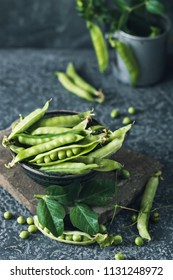 Unpeeled  green peas in bowl on dark stone background