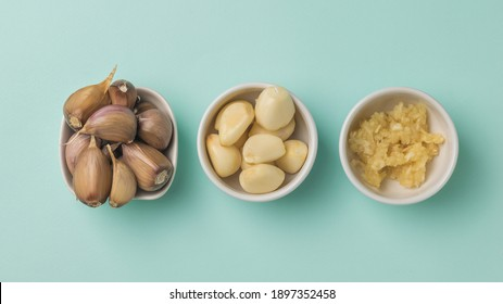 Unpeeled, peeled and grated garlic on a blue background. A popular spice for the kitchen.