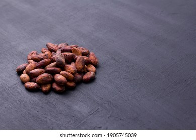 Unpeeled raw brown cocoa beans in heap lie On black modern concrete background. Flat lay, mock up, copy space. Raw materials for making cocoa powder, cocoa beverages, chocolate. Health drink concept.