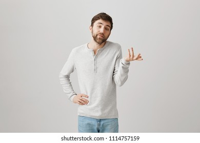 unpleasant caucasian male snob with beard, explaining something while gesturing with hands, making look as if he knows everything, standing over gray background. Gyt weighing up opportunities