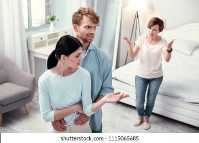Unpleasant cohabitation. Unhappy young couple standing together while listening to complains of the mother in law