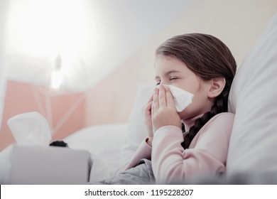 Unpleasant condition. Close up of small pale girl using napkins while keeping her eyes closed and sneezing