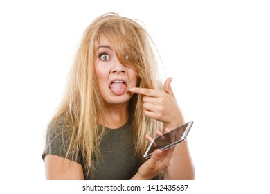 Unpleasant conversation, bad relationships, concept. Crazy young blonde weirdo woman with messy hair talking on phone pointing at tongue. Studio shot isolated