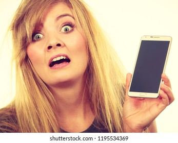 Unpleasant conversation, bad relationships, not knowing technology concept. Crazy young blonde weirdo woman with messy hair holding phone showing black screen. Studio shot isolated