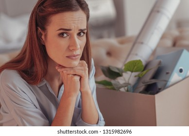 Unpleasant news. Close up of worried young woman with sadness in her eyes while propping her chin with hands and sitting on home sofa