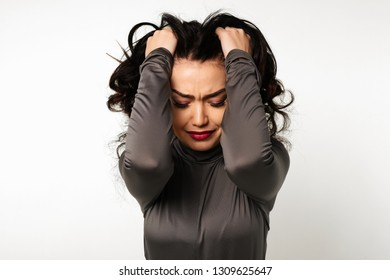 Unpleasant pain. Sad unhappy handsome woman holding his forehead while having headache isolated