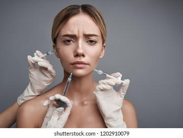 Unpleasant procedure. Upset young lady sitting against the grey background and frowning while getting unpleasant painful injections in her face
