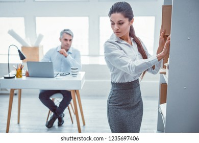 Unpleasant situation. Beautiful fit worker feeling anxious about her boss who staring at her back