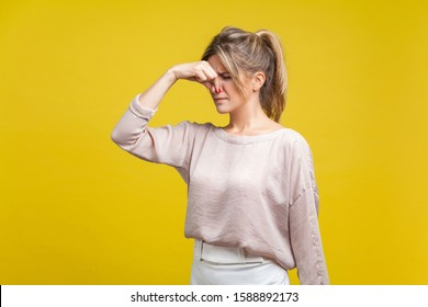 Unpleasant smell. Portrait of young dissatisfied woman with fair hair in casual beige blouse standing with closed eyes, pinching her nose with disgust. indoor studio shot isolated on yellow background