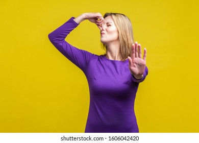 Unpleasant smell. Portrait of young woman in purple dress pinching her nose with fingers to hold breath, frowning in displeasure and showing stop gesture. studio shot isolated on yellow background