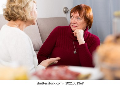 Unpleasantly surprised senior woman sitting on sofa listening her female friend