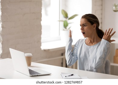 Unpleasantly surprised woman looking at laptop screen, sitting with raised hands, gesture, receiving bad unexpected news, outraged shocked businesswoman reading business email, bankruptcy