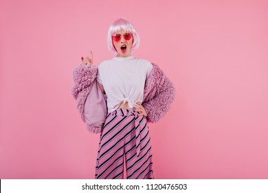 Unpleased female model in trendy fluffy jacket posing in studio. Attractive disappointed girl in pink periwig isolated on colorful background.