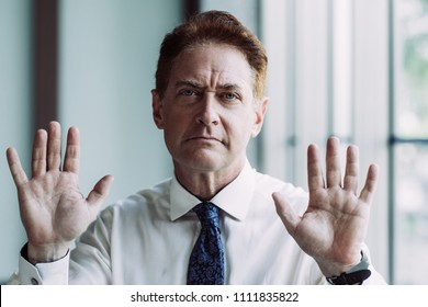 Unpleased mature businessman showing stop gesture with both hands. Serious entrepreneur surrendering and looking at camera. Business crime concept