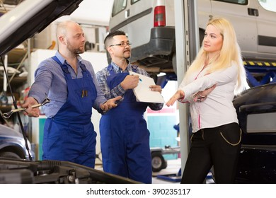 Unpleased young long-haired woman duping by troublemakers at auto service center. Selective focus