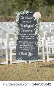 Unplegged Wedding ceremony sign with pink rose at outddoor weddi