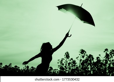 Unplugged free silhouette woman with umbrella up to green sky. Nature girl at windy rainy day has adventure wanderlust. Wonderful scene of imagination power and departure to new horizons in youth