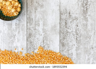 Unpopped corn kernals shot against a light wooden background with space for text, copyspace.  National Popcorn Day 19 January 2021