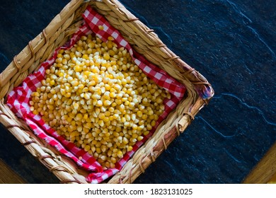 Unpopped popcorn in a basket on black background. A type of corn that expands from the kernel and puffs up when heated. Yellow seeds, edible, raw and vegan food. Isolated macro photo close up