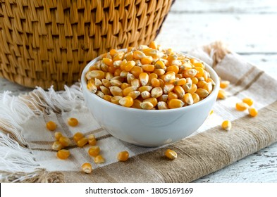 Unpopped popcorn kernals in white bowl.  Close up view with horizontal composition.
