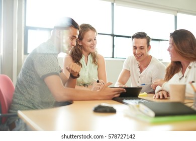 Unposed group of creative business entrepreneurs in an open concept office brainstorming together on a digital tablet.
