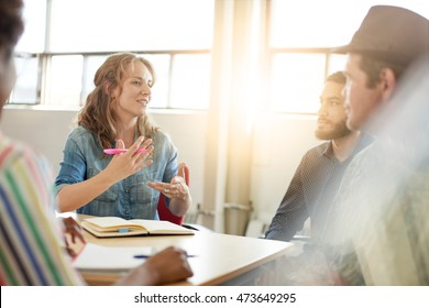 Unposed group of creative business people in an open concept office brainstorming their next project.