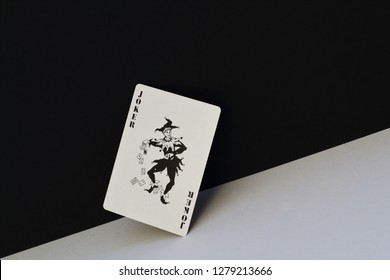 Unpredictable joker as symbol of opposites, contradictions of human nature. Black joker on contrasting white and black background.